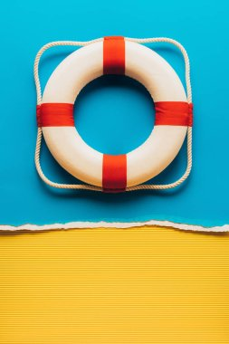 top view of red and white life saver on blue and yellow paper background