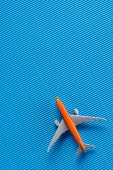 top view of toy plane on blue backdrop, trip concept