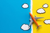 Photo top view of toy plane and paper clouds on yellow and blue background, trip concept