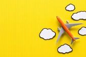 felülnézet játék gép, és felhők, sárga háttér, utazás koncepció papír