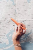 partial view of woman holding toy plane in hand with map on background, vacation concept