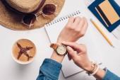 Oříznout záběr kontrola času žena u stolu s slaměný klobouk, sluneční brýle, cestovní pas a zápisník, cestování koncept