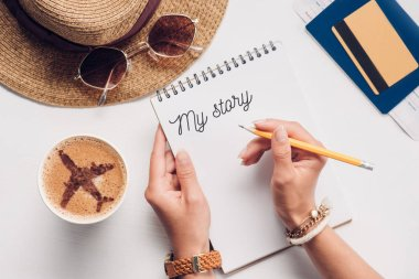 partial view of woman with notebook with my story lettering at tabletop with cup of coffee, straw hat, passport and ticket, traveling concept