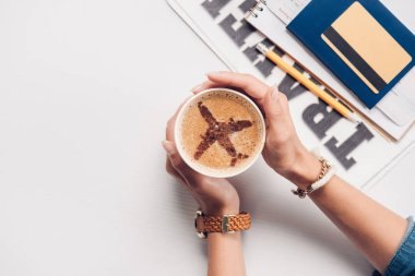 cropped shot of woman holding cup of coffee with plane sign at tabletop with credit card, passport and ticket, traveling concept