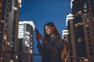 smiling woman with backpack using smartphone on street with night city lights on background