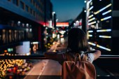 rear view of woman with backpack standing on street and looking at night city lights