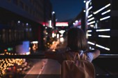 back view of woman with backpack standing on street and looking at night city lights