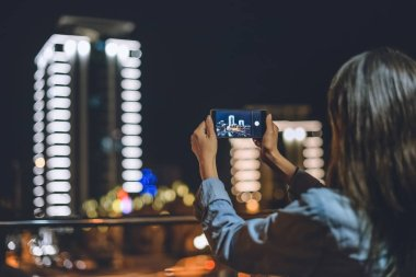 back view of woman taking picture of city on smartphone in hands at night