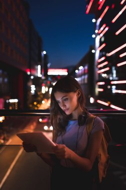 portrait of young woman with headphones using tablet on street with night city lights on background