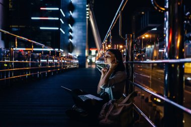side view of woman listening music in headphones with laptop on knees on city street at night