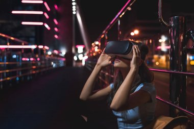 young woman in virtual reality headset sitting on street with night city on background