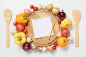 Fotografie top view of ripe vegetables around wooden board, notebook and pencil isolated on white