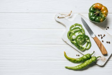 top view of chili and bell peppers on white wooden table