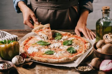 partial view of woman in apron taking piece of pizza on cutting board on wooden tabletop