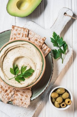 top view of hummus with parsley, olives, pita bread and avocado on wooden tabletop