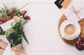 flat lay with wrapped bouquet of flowers, cup of coffee and credit card on white wooden tabletop