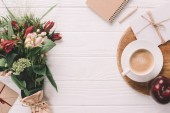 flat lay with wrapped bouquet of flowers, cup of coffee and notebook on white wooden tabletop