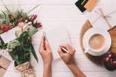 Fotografie partial view of woman making notes in notebook at tabletop with bouquet of flowers and cup of coffee