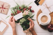 partial view of woman with blank card at tabletop with bouquet of flowers, cup of coffee and credit card