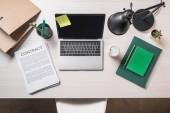 pohled laptop, papír šálek kávy, smlouvy a šablon na stole