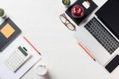 pohled shora pracoviště s kalkulačka, papírnictví, kávy a digitálních přístrojů na stole