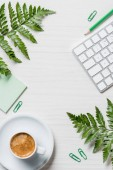 elevated view of coffee cup, fern leaves, stationery and computer keyboard on table