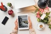 Oříznout obrázek ženské volné noze drží digitální tablet s lístky na obrazovce u stolu s šálek kávy, miniaplikací a květy s blahopřáním