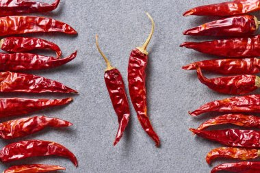 top view of dried red chili peppers arranged on grey tabletop