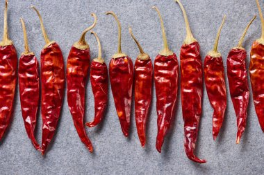 top view of red chili peppers arranged on grey tabletop