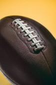 Fotografia Chiuda in su della sfera di football americano marrone isolato su colore giallo