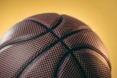 Fotografie Detailní záběr z hnědé basketbalový míč izolované na žluté
