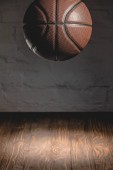 Fotografie brown basketball ball falling on wooden floor