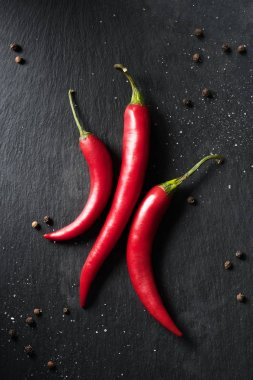 top view of three red ripe chili peppers on black surface