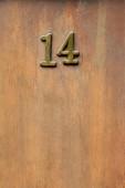 Fotografie Nahaufnahme von 14 Zeichen auf Holztür