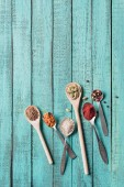 Fotografie top view of spoons with various dried aromatic spices on turquoise wooden surface