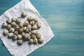 Photo fresh organic quail eggs on white cloth on turquoise wooden table