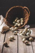Fotografie organic quail eggs in wicker basket and feather on wooden table