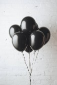 bunch of black balloons on ribbons in front of white brick wall