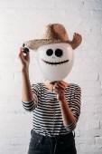 Fotografia donna che tiene aerostato di halloween con cappello di paglia davanti alla testa