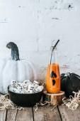 Photo close-up shot of halloween composition with pumpkins, marshmallows and bottle of pumpkin juice