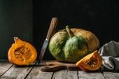 Fotografie pohled ze složení potravin s dýní, nůž a prkénko na dřevěný povrch na tmavém pozadí na plochu