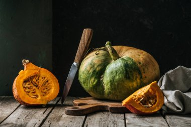 close up view of food composition with pumpkins, knife and cutting board on wooden surface on dark background