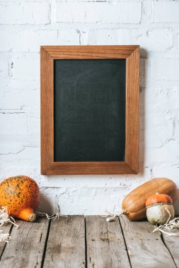 close up view of raw pumpkins on wooden tabletop and blank chalkboard hanging on white brick wall