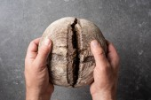 Fotografia ritagliata colpo delluomo che tiene la pagnotta di pane di segale in mani sul contesto grigio