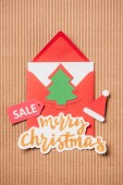 elevated view of greeting envelope, lettering sale and merry christmas on surface