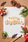 Fotografie pohled shora prázdného papíru, stálezelené kužely, zdobené dárkové krabičky a nápisem Veselé Vánoce na povrchu