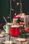 nő tartja karácsonyi mézeskalács ember, a kakaót a marshmallows, a fából készült asztal fény koszorú