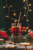 Fotografie glass of mulled wine on wooden stump with gingerbread and christmas light garland