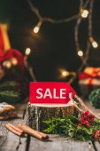 Fotografia modifica di vendita di Natale rosso sul ceppo di legno con bastoncini di cannella e ghirlanda di luce