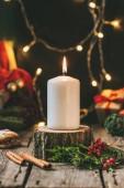 Weihnachtskerze auf Holzstumpf mit Lichterkranz